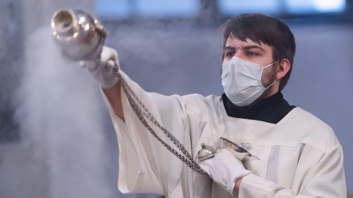 Ministrant mit Mundschutz schwenkt Weihrauchfass