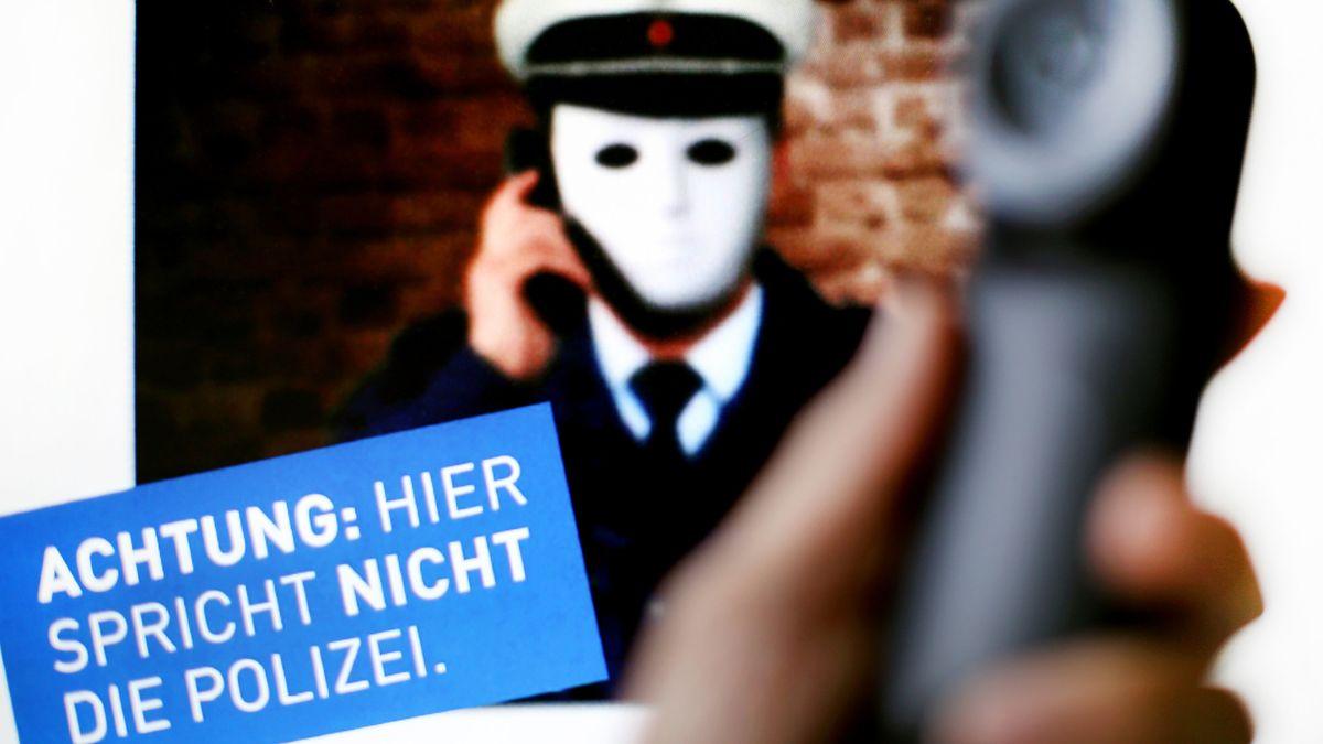 Illustration - Ein Telefonhörer ist vor einem Plakat der Polizei mit der Aufschrift «Achtung: Hier spricht nicht die Polizei» zu sehen.