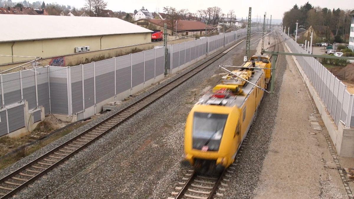 Ein gelber Zug fährt euf einer zweispurigen Gleisanlage