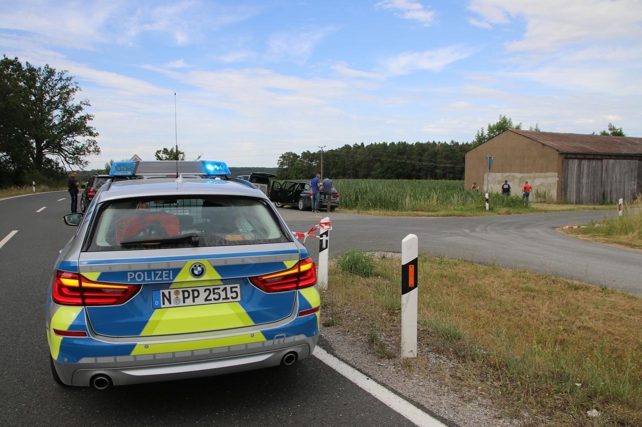 Kennzeichendieb Rosenberg: Ein Polizeiauto steht auf einer Straße, Beamten kontrollieren.