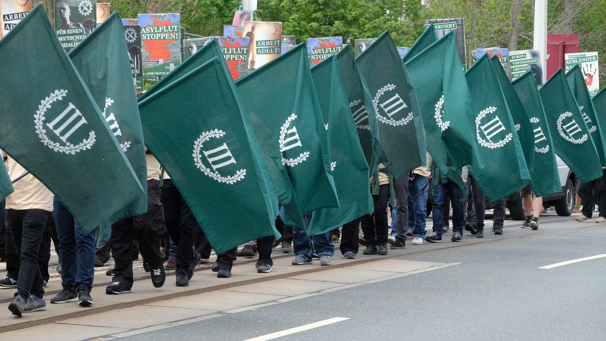 """01.05.2019, Sachsen, Plauen: Teilnehmer eines rechten Aufmarsches der Partei """"Der dritte Weg"""" gehen eine Straße entlang."""