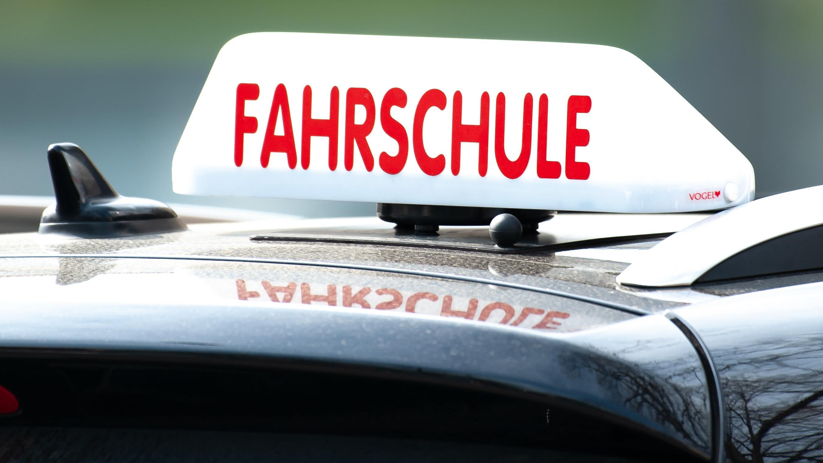 """Schild """"Fahrschule"""" auf einem Autodach"""