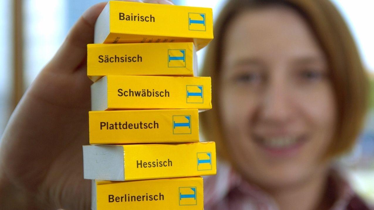 Frau hält Dialekt-Wörterbücher in der Hand