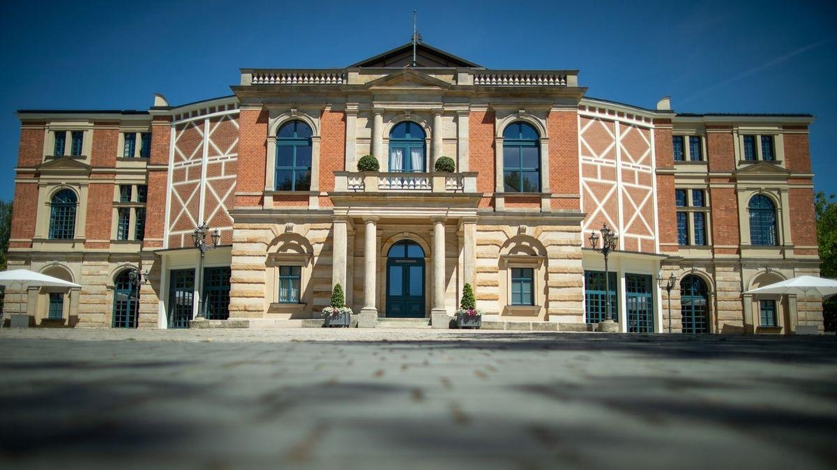 Das Bayreuther Festspielhaus, vor dem zwei weiße Sonnenschirme stehen.