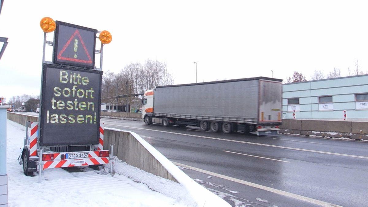 """""""Bitte sofort testen lassen"""" steht auf einer mobilen Anzeigetafel an einem Straßenrand"""