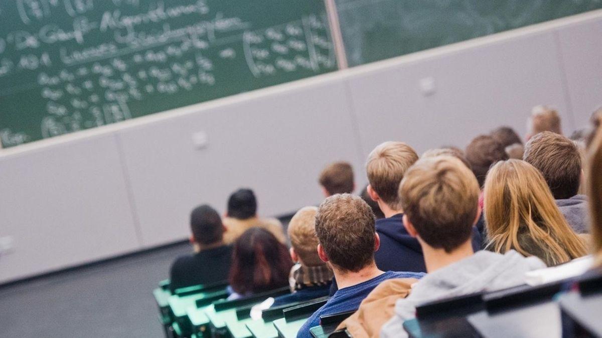 Studierende sitzen im Hörsaal in einer Hochschule und schauen in Richtung Tafel.