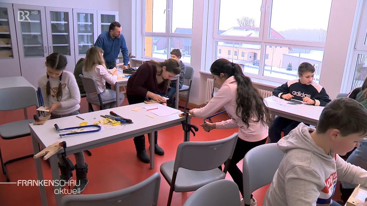 Schüler probieren das Arbeiten mit Werkzeugen aus.