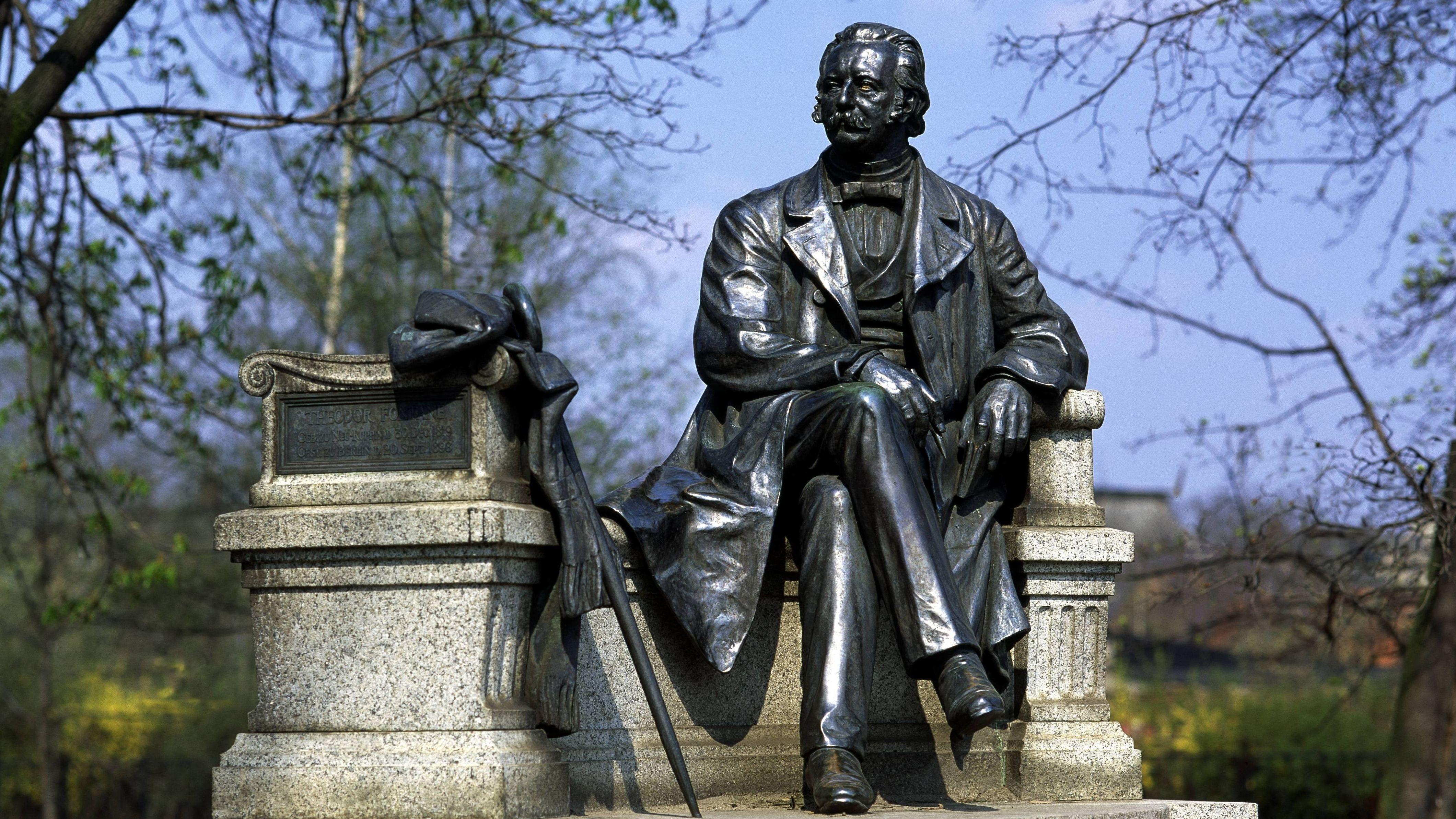 Das bronzene Fontane-Denkmal in Neuruppin zeigt den Autor lebensgroß und in sitzender Pose auf einer Steinbank.