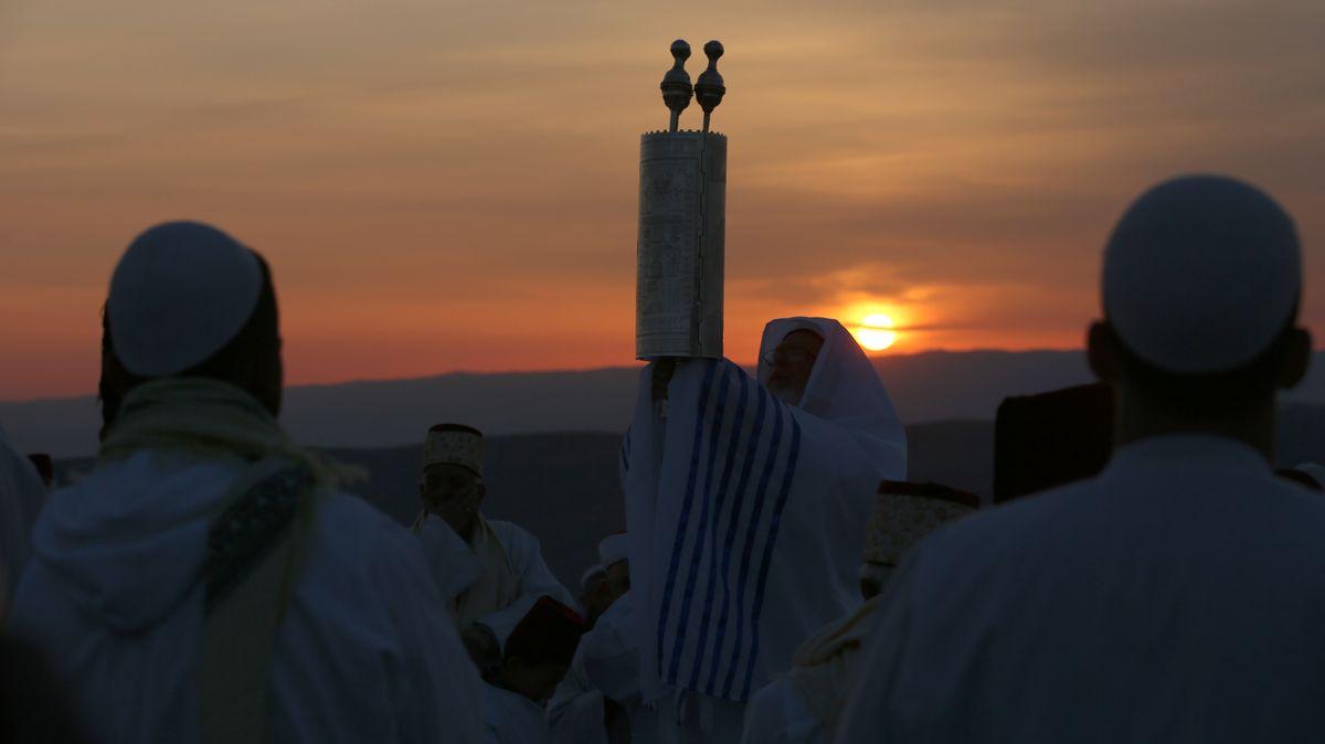 Ein Priester der samaritanischen Gemeinschaft hebt vor einem Morgengebet auf dem Berg Garizim eine Thora-Schriftrolle in die Höhe.