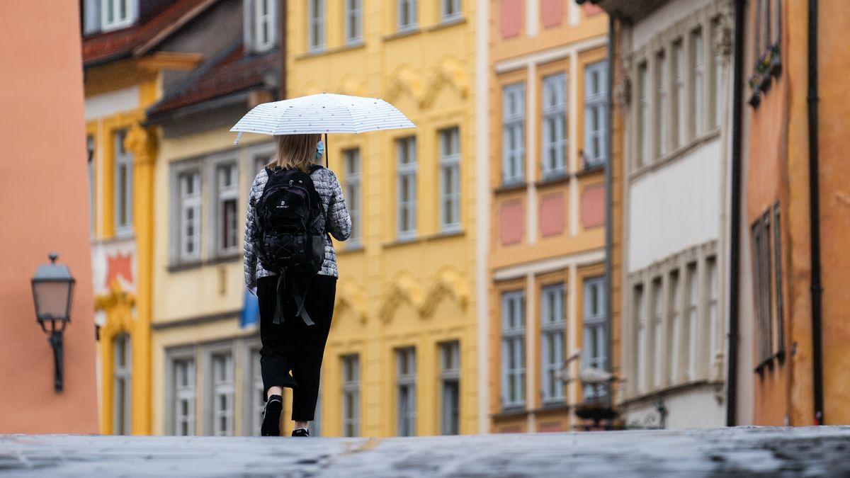 Eine Frau geht mit Regenschirm durch die Innenstadt von Bamberg.