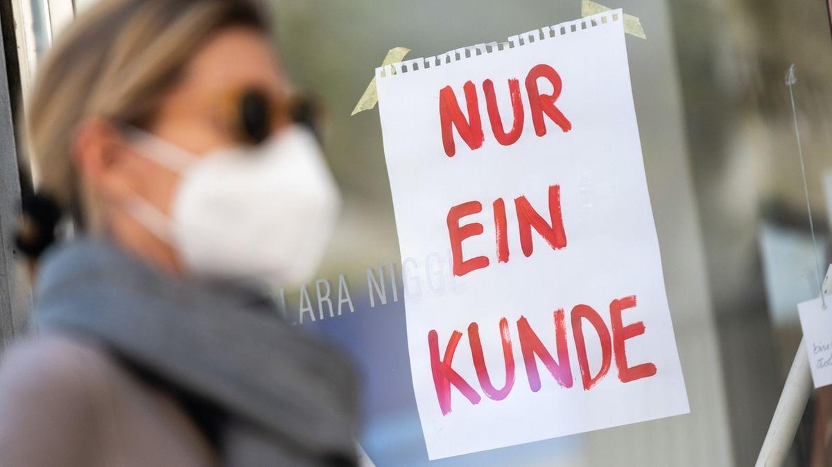 Frau mit Maske vor einem Geschäft. (Symbolbild)