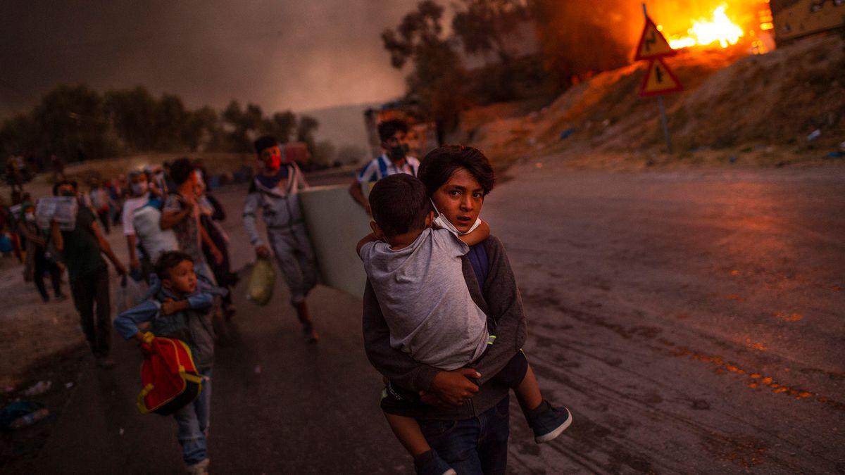 Ein Junge trägt ein Kind auf dem Arm, im Hintergrund weitere Flüchtlinge und Flammen.