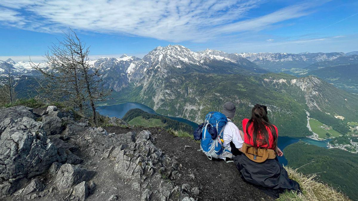 Zwei Wanderer sitzen auf dem Jenner und blicken in das Berchtesgadener Land.