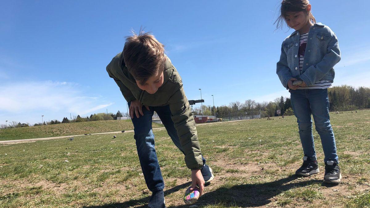 Sebastian legt einen selbst bemalten Stein ab, während seine Schwester Julia ihm zusieht