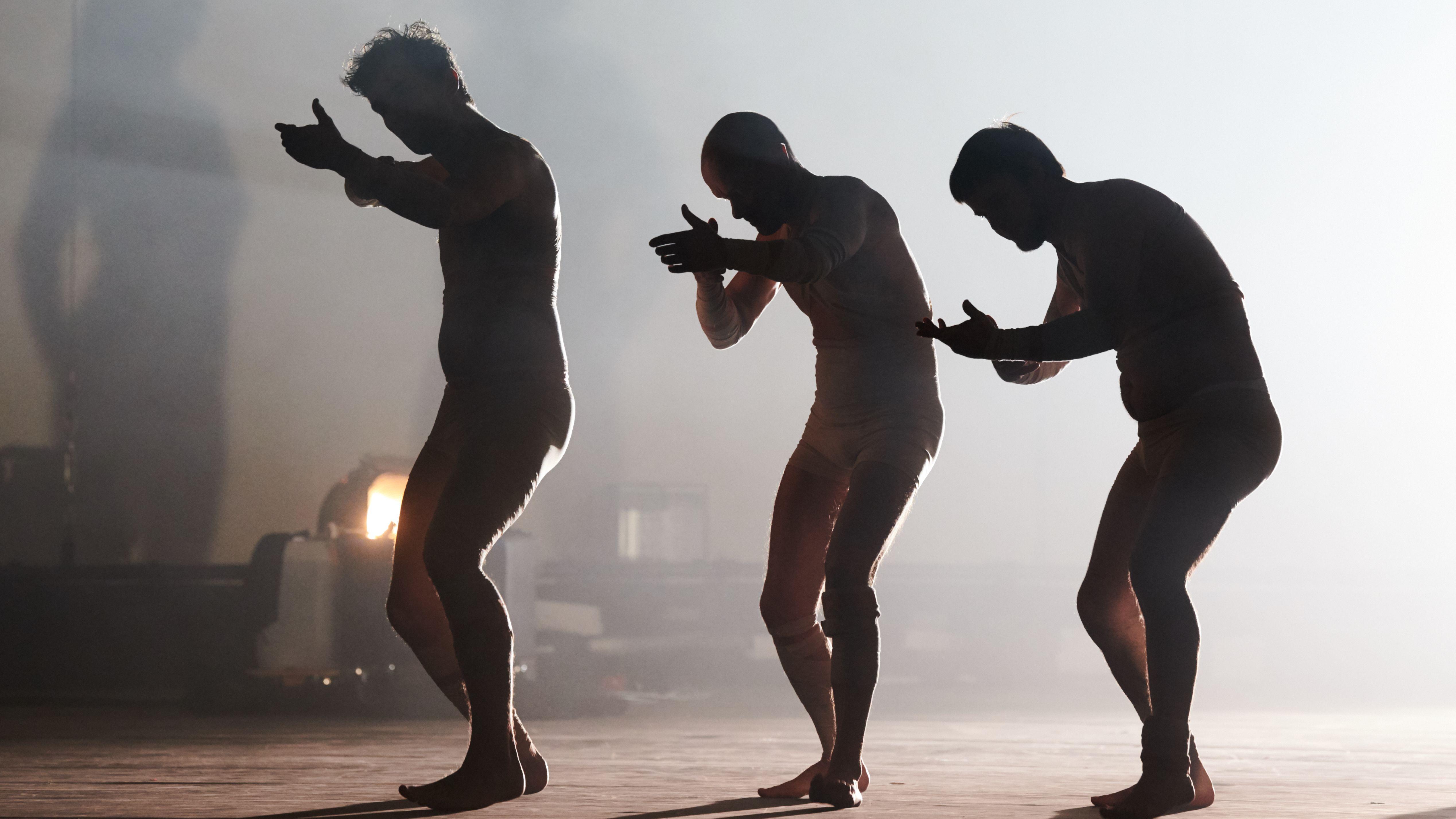 Auf der Bühne sind drei Schauspieler nur als schemenhafte Silhoutten zu erkennen.