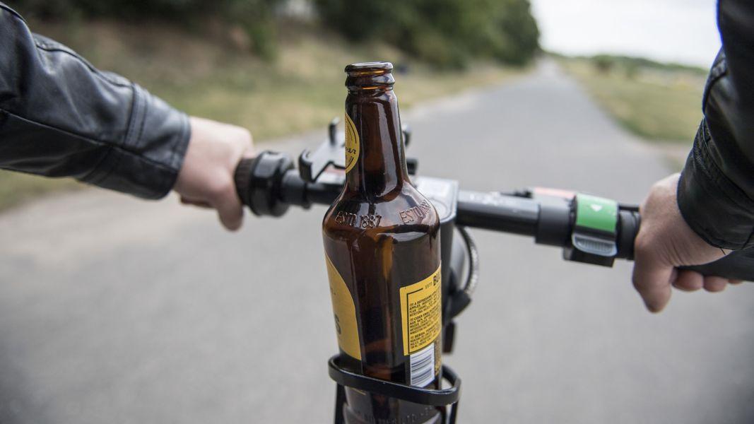 Eine Bierflasche steht in einer Getränkehalterung auf einem E-Scooter.