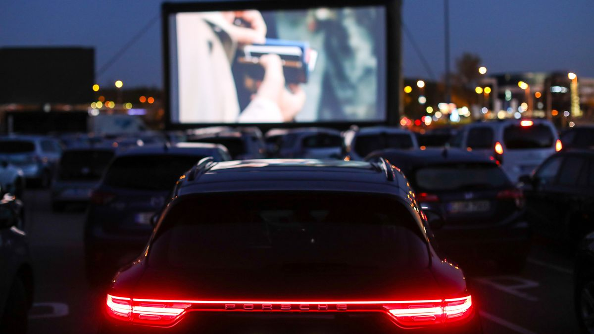 Besucher eines Autokino stehen mit ihren Autos vor einer Leinwand (Symbolbild)