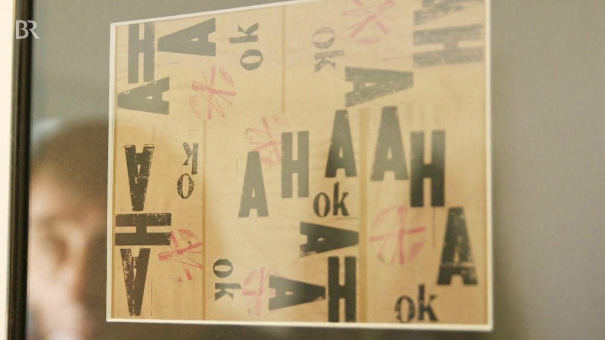 """Eine Tafel mit Aufschriften """"Aha Okay"""" hängt an einer Wand"""