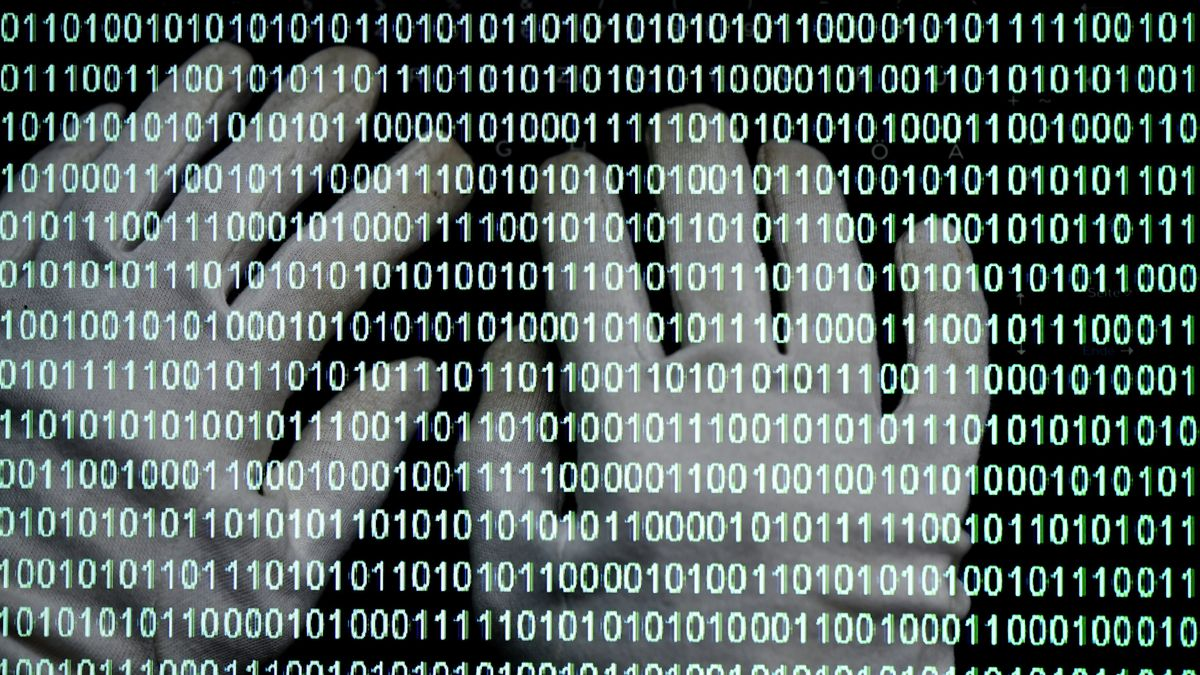 Monitor mit Binärcode und Händen mit Handschuhen