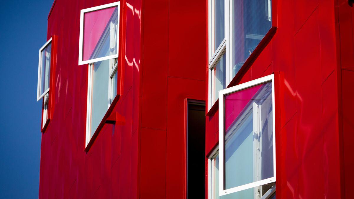 Rotes modernes Gebäude mit offenen Fenstern.