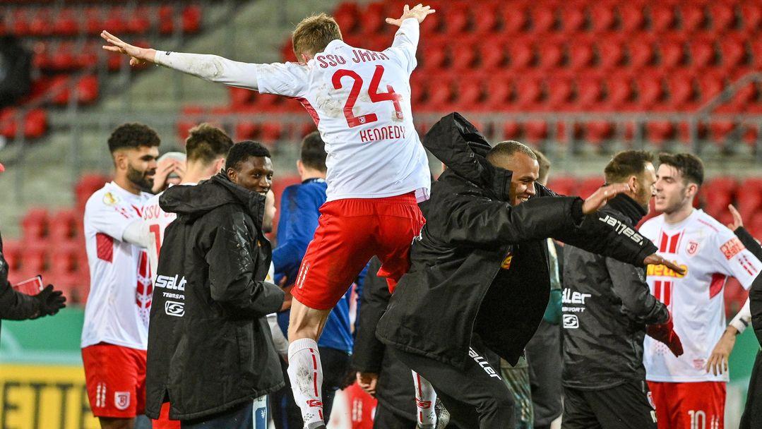 Spieler des SSV Jahn Regensburg bejubeln Sieg gegen den 1. FC Köln.