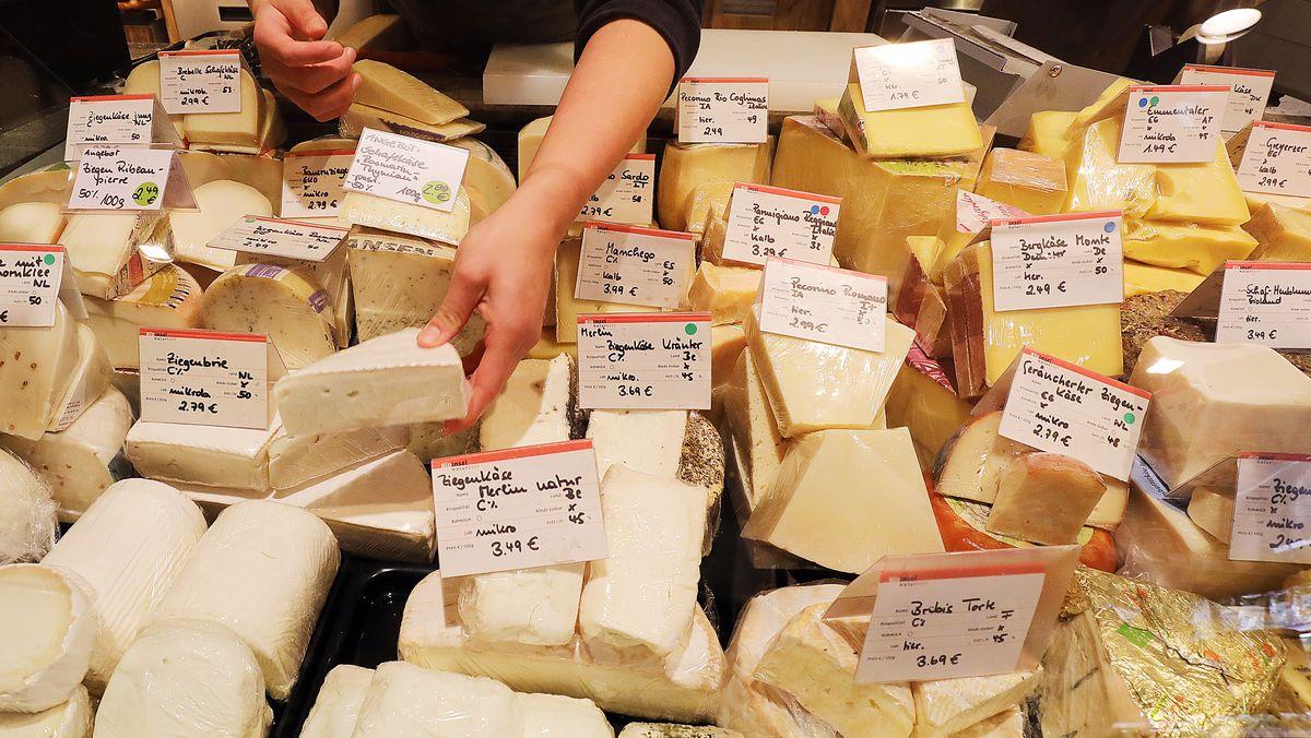 An einer Käsetheke wird eine Kundin bedient.