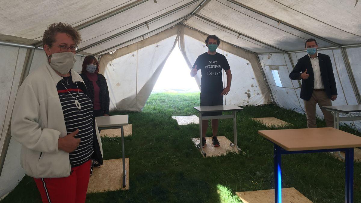 Schulleiter Stephan Ludl und drei weitere Personen stehen in einem der Festzelte mit Schulbänken und zeigen den Daumen nach oben.