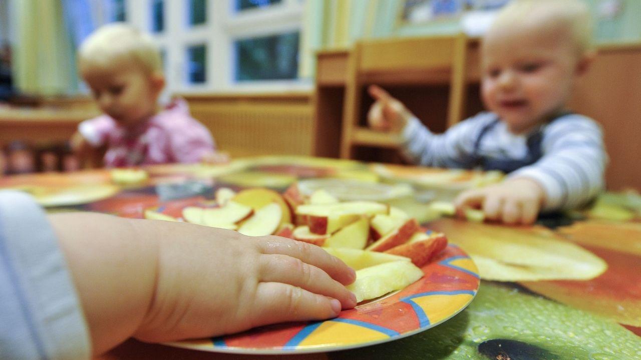 Kinder sitzen in einer Kinderkrippe am Tisch und essen.