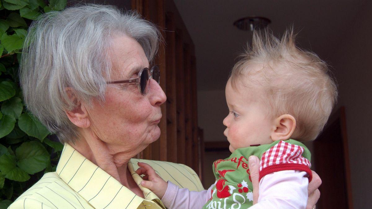 Porträt einer Großmutter mit ihrer kleinen Enkelin. Die ältere Dame hält das noch verschlafene kleine Mädchen auf dem Arm und sucht den Blickkontakt. Dem Kind stehen die Haare etwas zu Berge und es schaut trotz der gut gemeinten Zuwendung der Oma etwas verstört und missmutig an ihr vorbei.