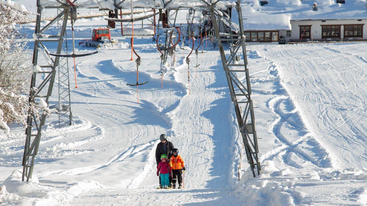 Der Skilift und Personen im Schnee.