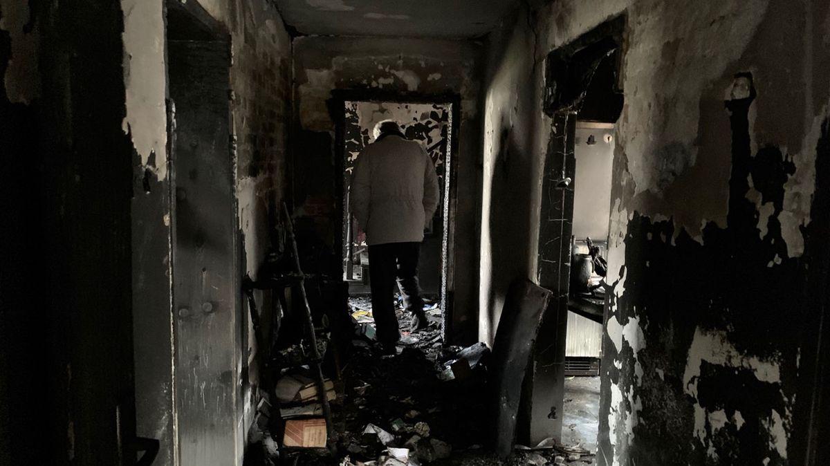 Ein Mann läuft durch ein abgebranntes Haus.