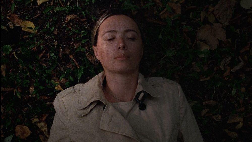"""Szenenbild aus Déa Kulumbegashvilis Spielfilmdebüt """"Beginning"""": Es ist Nacht, eine Frau im Sommermantel liegt auf dem Rücken auf dem Waldboden. Ihre Augen hat sie geschlossen."""