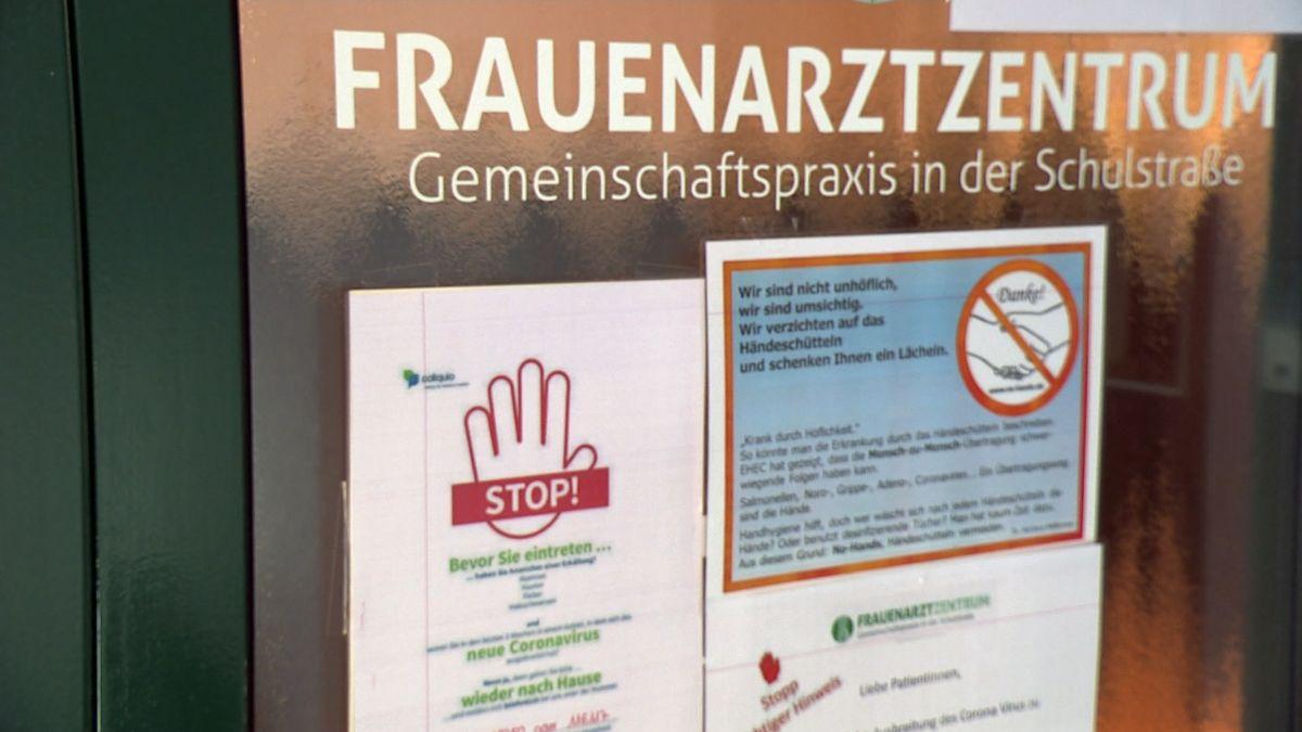 """Ein Hinweis mit einer Hand, unter der """"stop"""" steht, hängt an der Tür einer Frauenarztpraxis."""