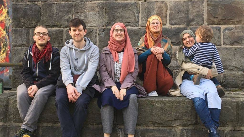 Zwei Männer, drei Frauen und ein Kind sitzen auf einer Mauer.
