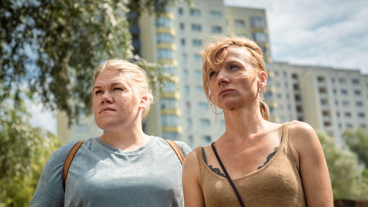 Zwei Schwestern stehen vor einem Sozialbau und schauen kämpferisch in die Ferne.