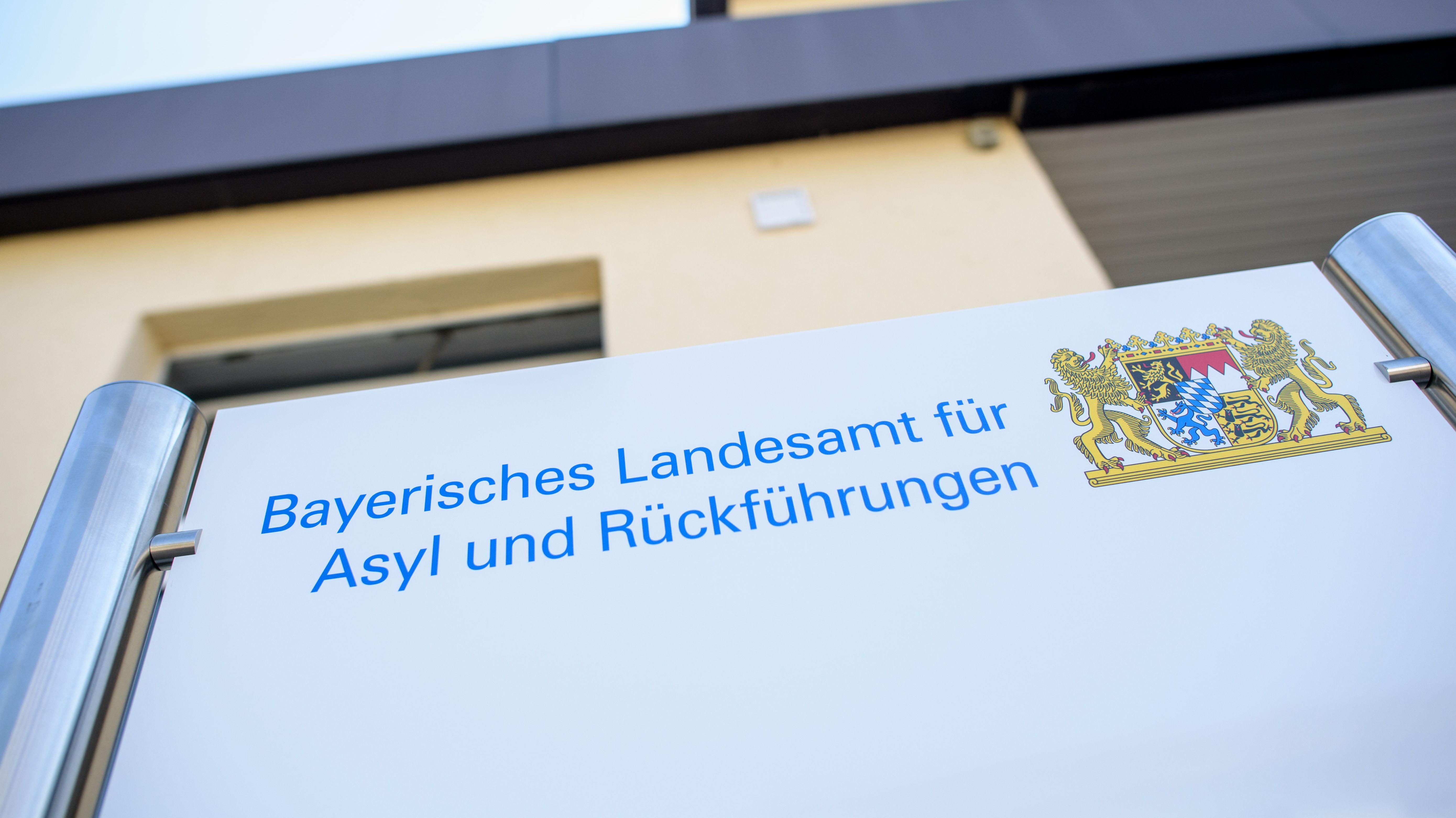 """Ein Schild mit der Aufschrift """"Bayerisches Landesamt für Asyl und Rückführungen"""" ist im Transitzentrum Manching vor dem Gebäude zu sehen."""