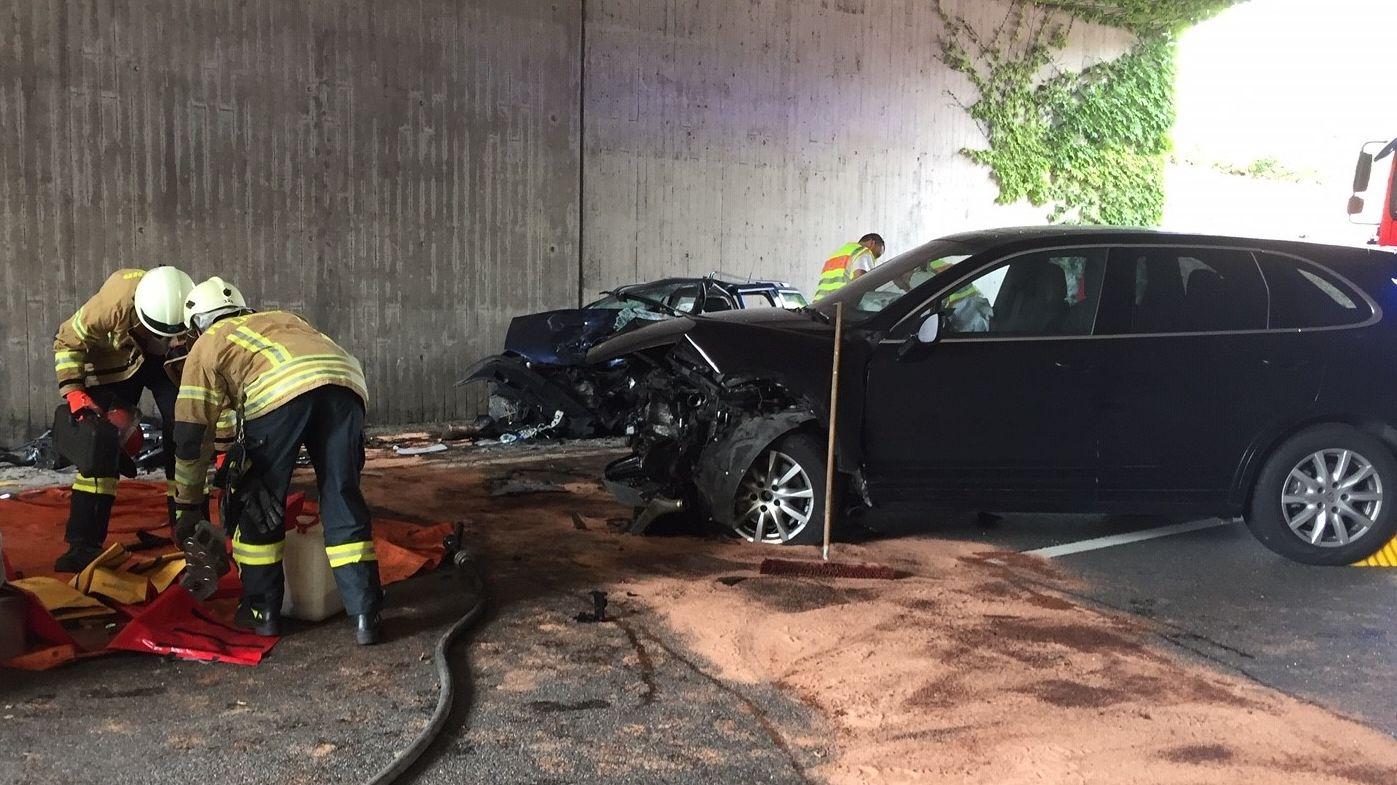 Die beiden Unfallautos stehen neben einer Betonwand