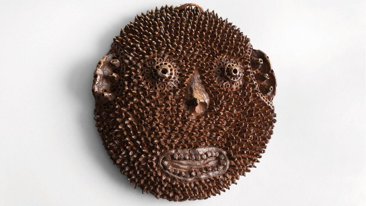 Maskenhaftes kreisrundes Gesicht aus brauner Keramik, von einer Art Stacheln besetzt