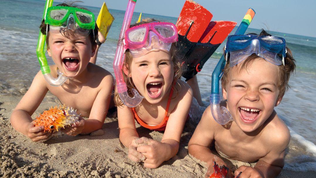 Drei Kinder liegen am Strand mit Taucherbrillen, Schnorcheln und Flossen im Wasser und strahlen glücklich in die Kamera (Symbolbild)
