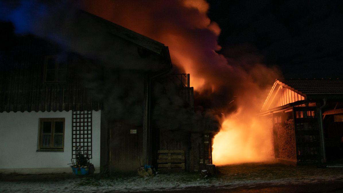 Im Vordergrund ein Gebäude bei Nacht, dahinter der Feuerschein und Rauch
