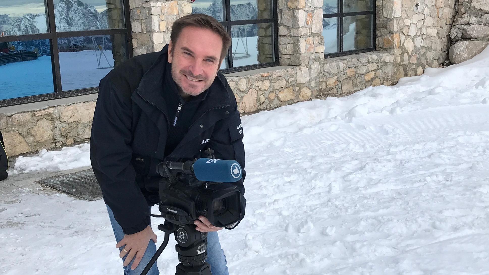 BR-Reporter Martin Breitkopf auf der Zugspitze mit Kamera auf Stativ.