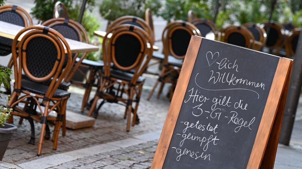 """Tafel mit der Aufschrift """"Herzlich Willkommen. Hier gilt die 3-G-Regel - getestet -geimpft - genesen"""" vor einem Cafe   Bild:pa/dpa/Arne Dedert"""