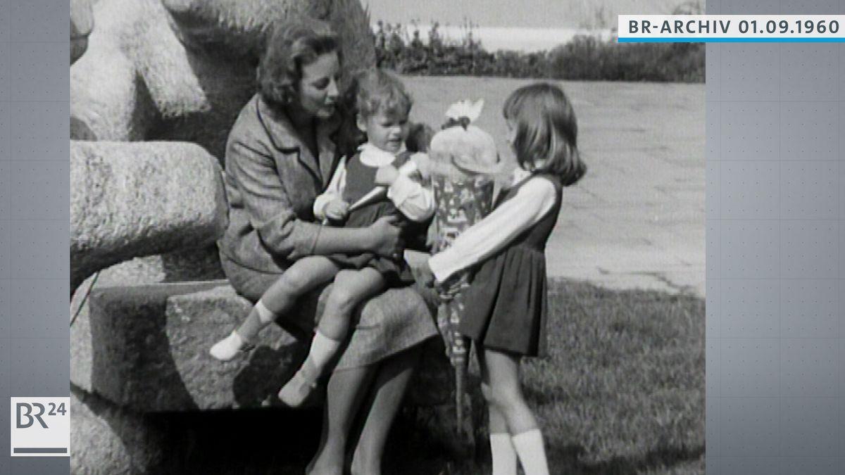 Ruth Kappelsberger mit einem kleinen Mädchen auf dem Schoß, daneben eine  Erstklässlerin mit Schultüte