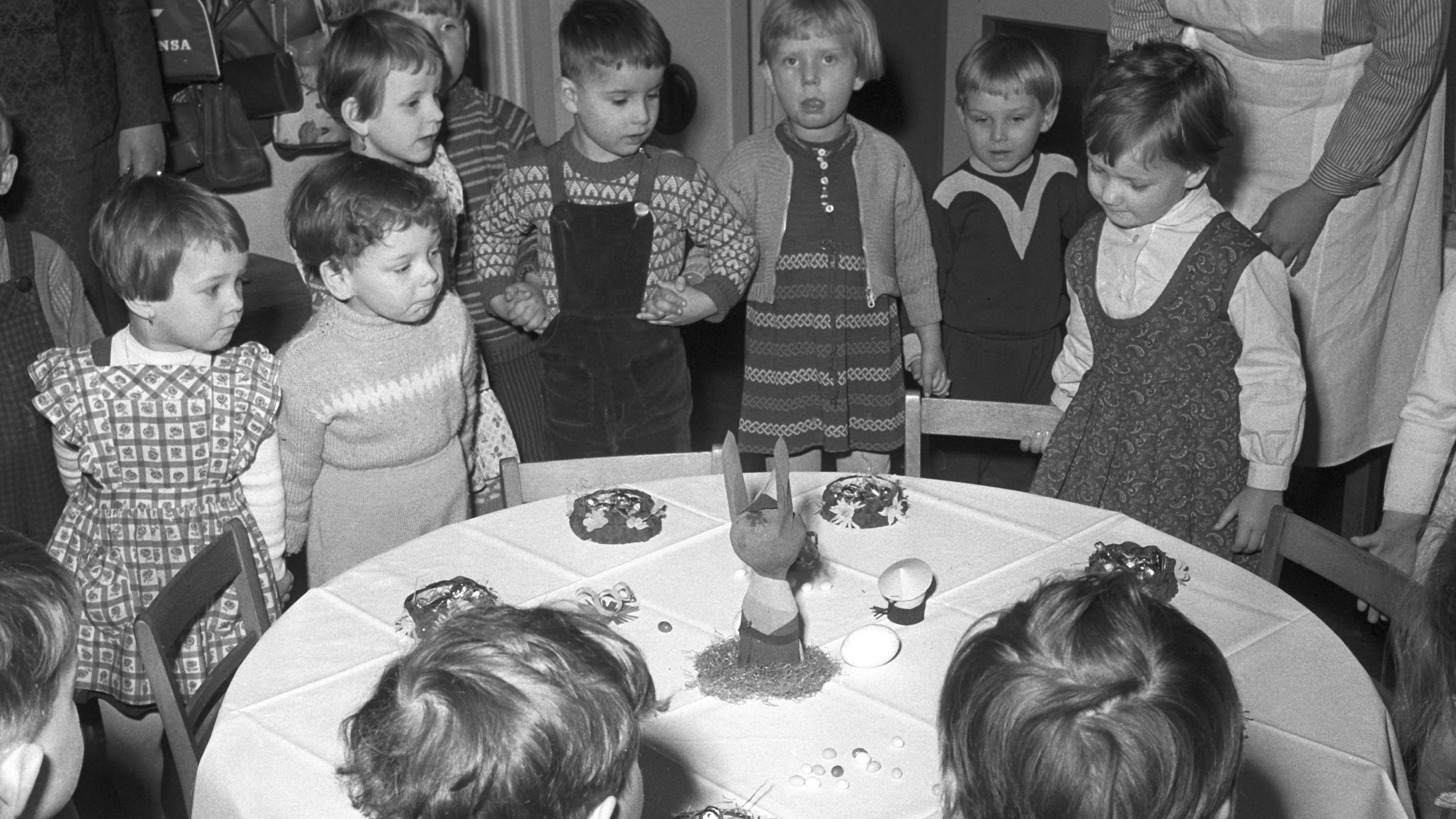 Heimkinder stehen zum Osterfest um einen Tisch herum und halten sich an den Händen fest.