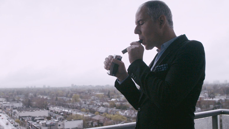 Ein Mann im Anzug steht auf einem Balkon und zündet sich eine Zigarre an.