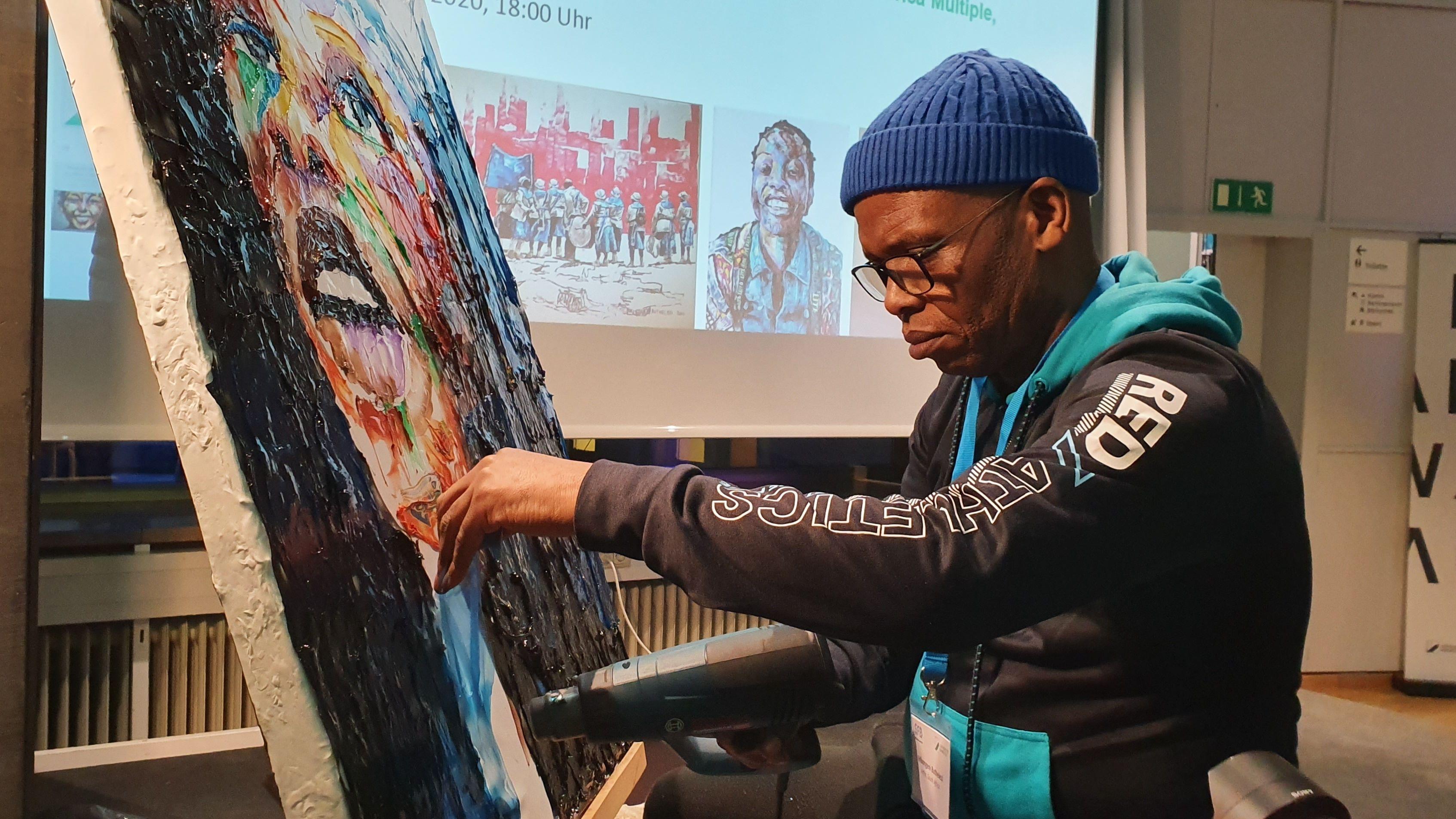 Der Künstler Mbongeni Buthelezi steht vor einer Leinwand, auf der ein buntes Gesicht aus Mikroplatik gemalt hat.