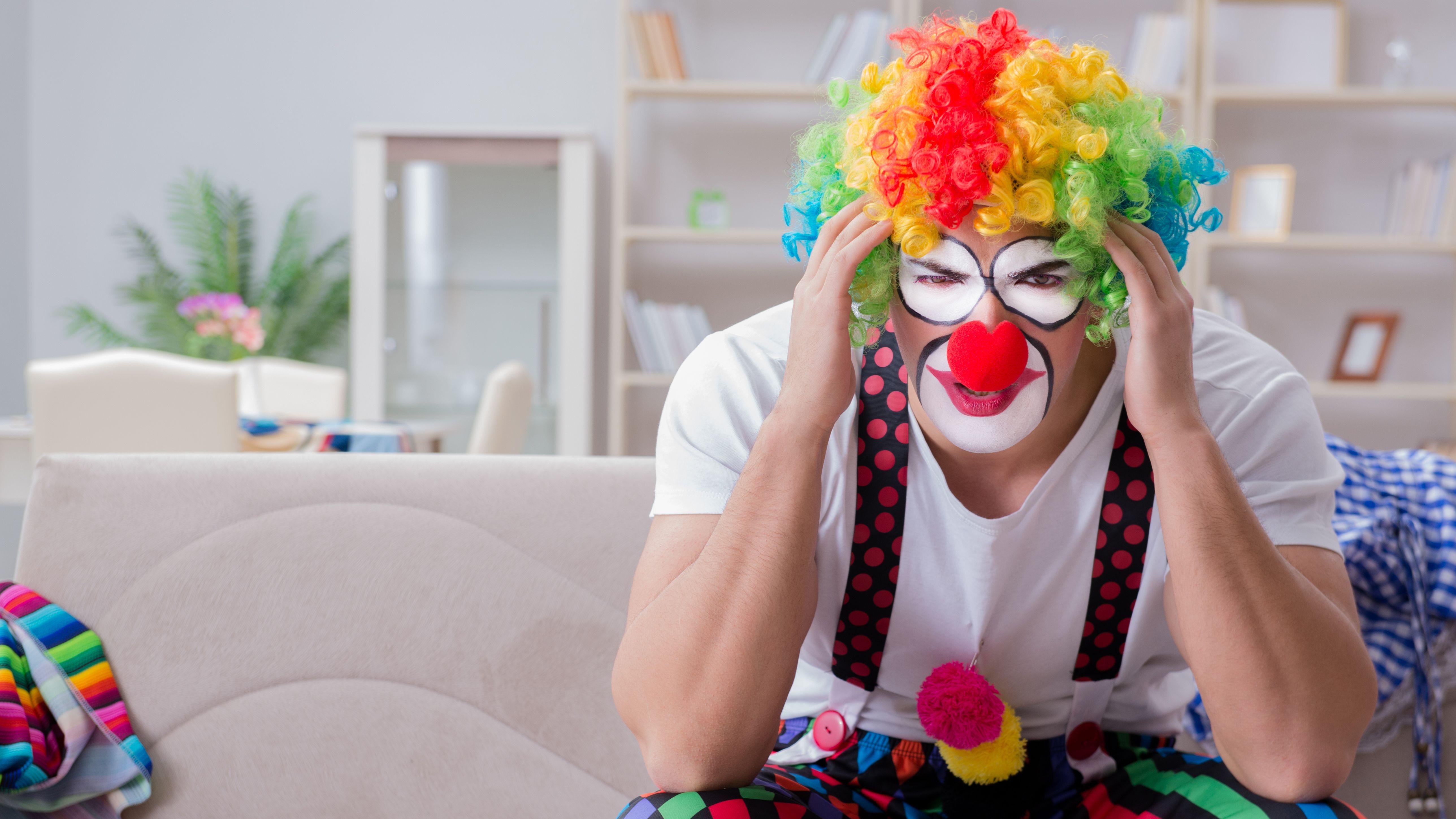 Clown sitzt auf einem Sofa und hält sich schmerzverzerrt den Kopf