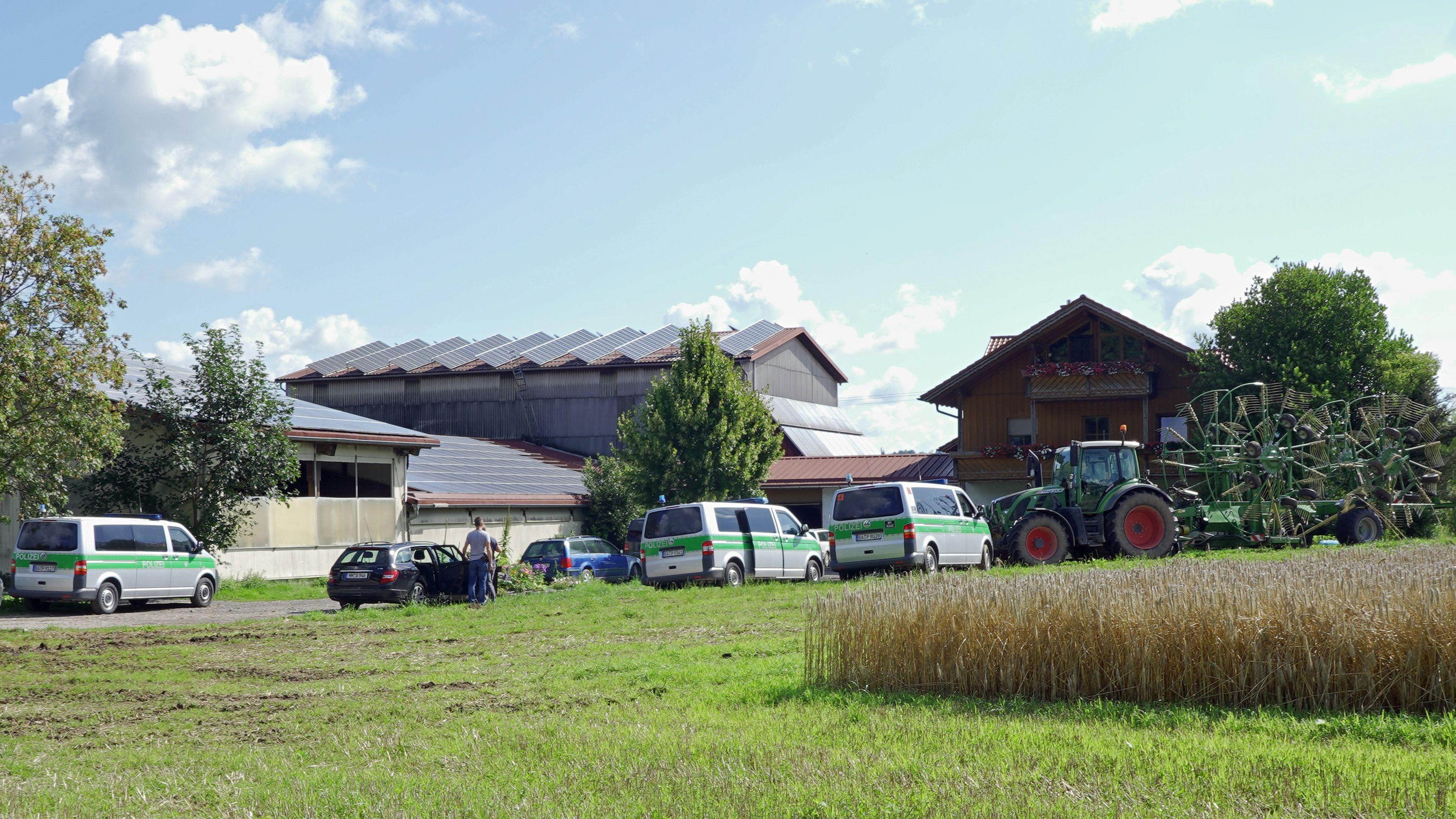Während einer Durchsuchung stehen Polizeifahrzeuge an einem Bauernhof in Bad Grönenbach