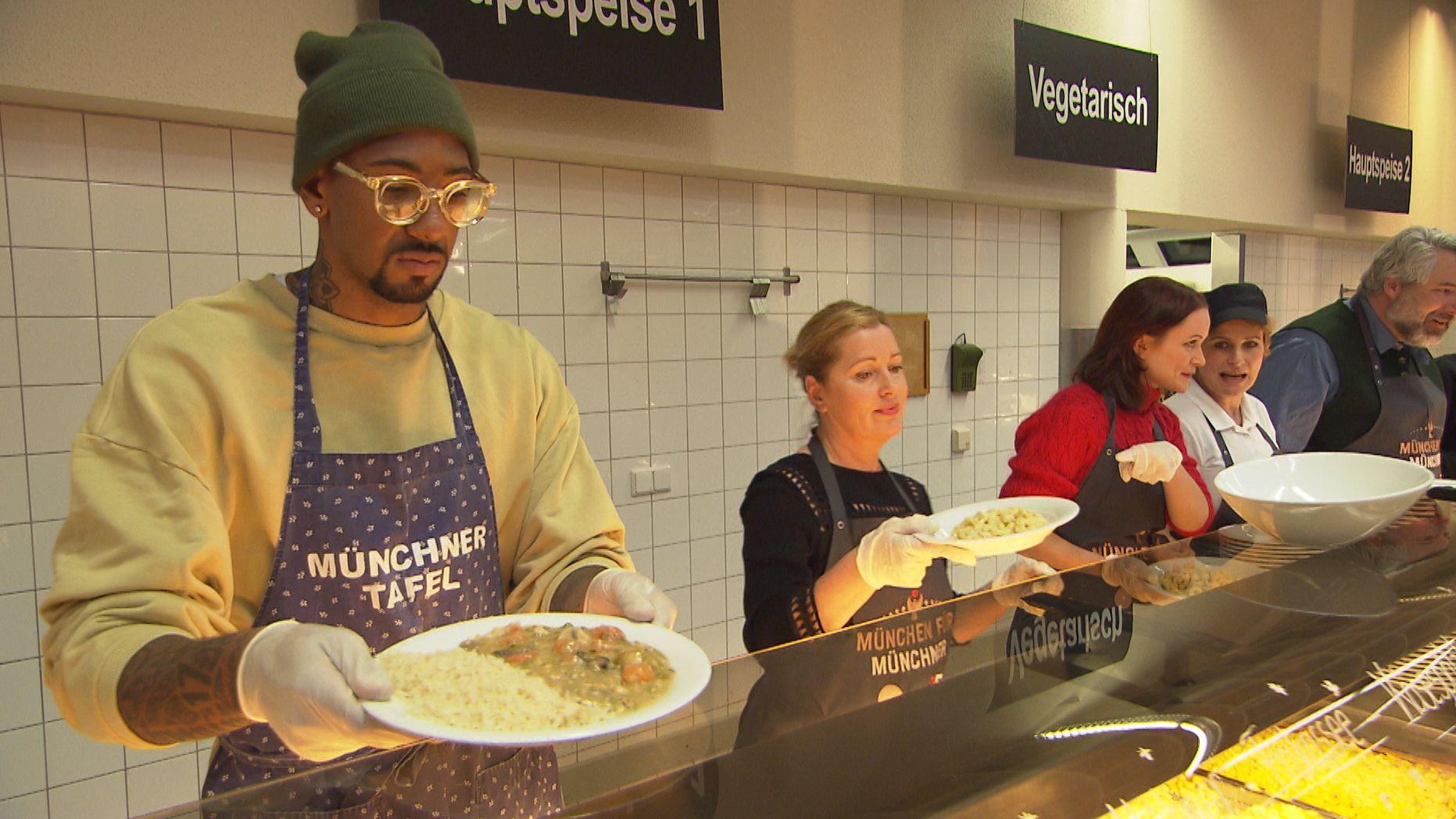 Promis geben Speisen bei der Münchner Tafel aus.
