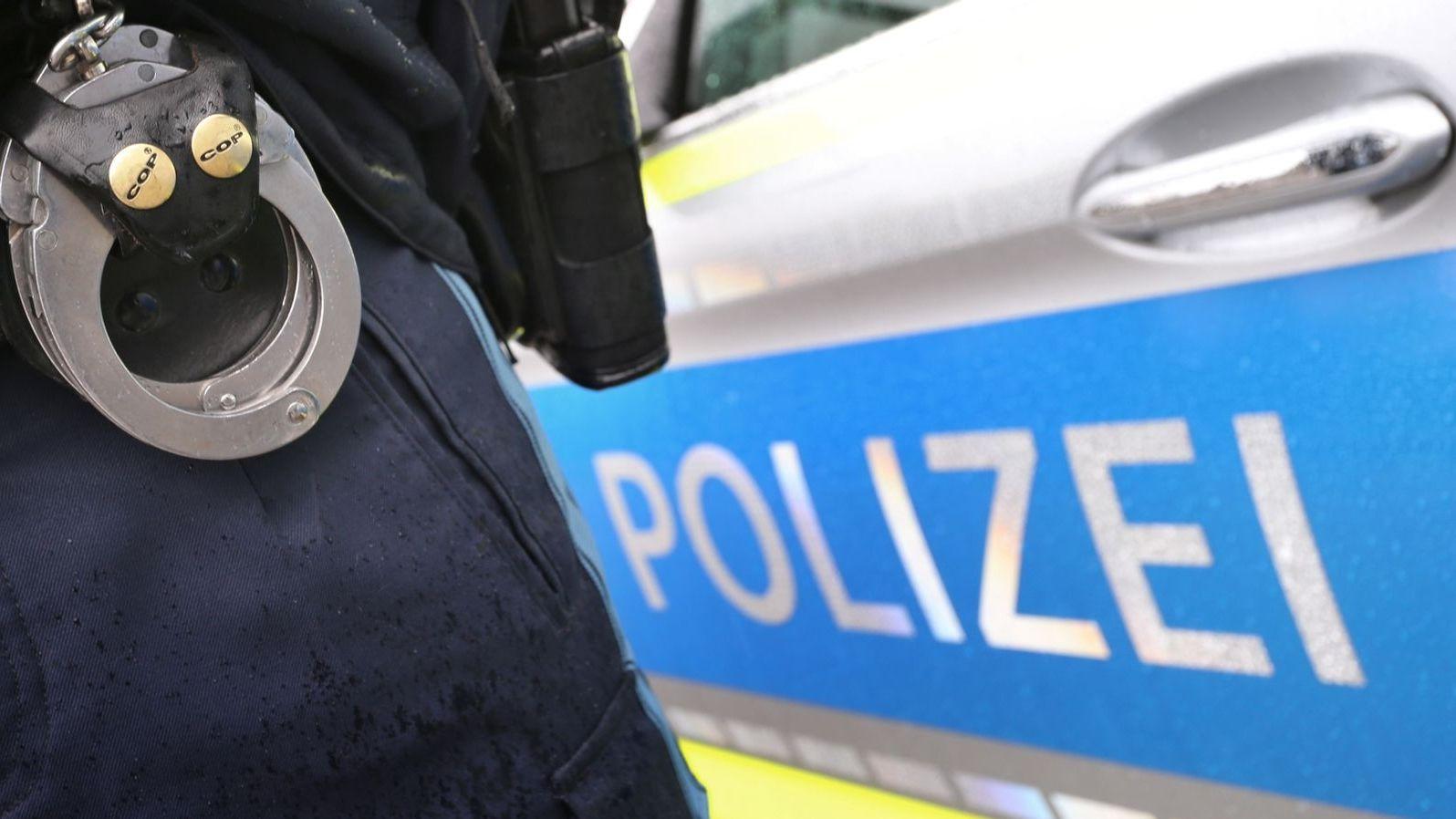 Handschellen eines Polizisten vor einem Polizeiauto